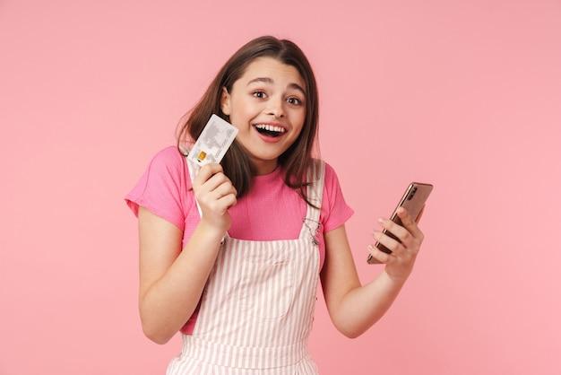 Adolescente feliz em pé isolada, mostrando um cartão de crédito de plástico e um celular, fazendo compras