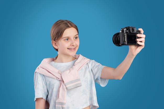 Adolescente feliz em uma camiseta branca em pé contra um fundo azul e se fotografando na fotocâmera isolada