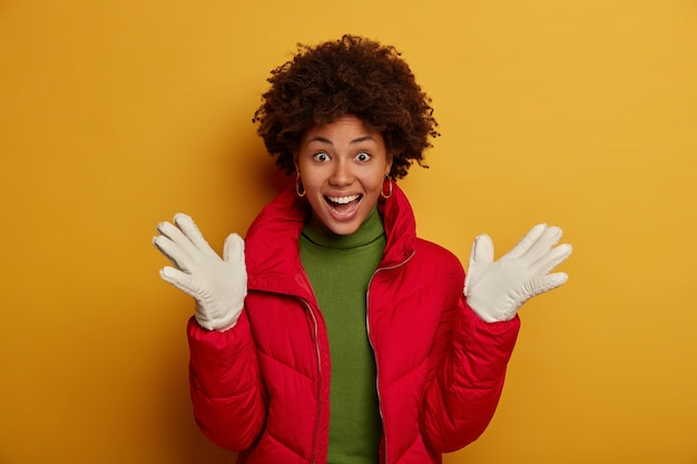 Adolescente feliz espalha as palmas das mãos, alegra-se com a primeira neve, usa um casaco vermelho e luvas brancas, ri alegremente durante o inverno, fica de pé sobre a parede amarela do estúdio.