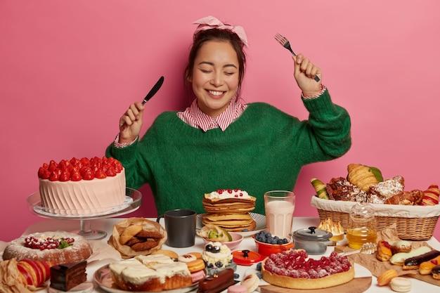 Adolescente feliz gosta de um evento festivo, senta-se à mesa com vários bolos gourmet, bebidas e biscoitos, segura uma faca e um garfo, obtém emoções agradáveis depois de tirar uma soneca de açúcar.
