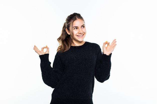 Adolescente feliz mostrando sinal de ok isolado na parede branca
