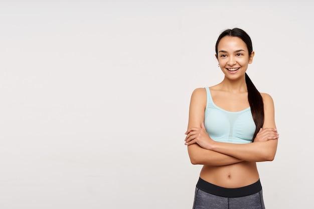 Adolescente, feliz procura mulher asiática com cabelo comprido escuro. vestindo roupas esportivas e sorrindo com os braços cruzados sobre o peito. observando à esquerda no espaço da cópia, isolado sobre fundo branco
