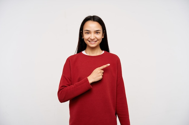 Adolescente, feliz procura mulher asiática com cabelo comprido escuro. vestindo um suéter vermelho e apontando para a direita no espaço da cópia, sorrindo confiante. assistindo a câmera isolada sobre fundo branco