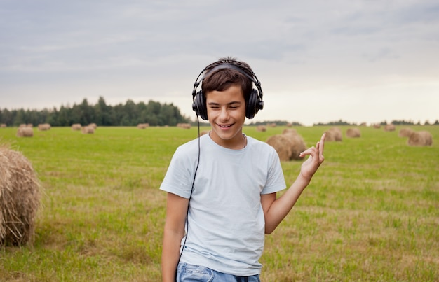 Adolescente feliz que escuta a música no campo.