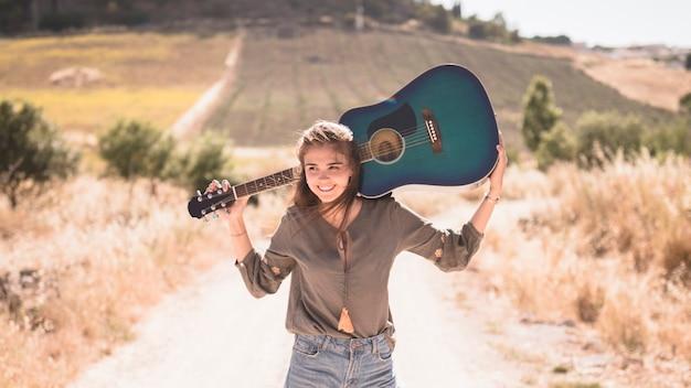 Adolescente feliz segurando a guitarra ao ar livre