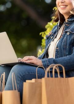 Adolescente feliz segurando seu laptop ao ar livre
