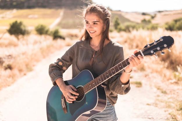 Adolescente feliz tocando guitarra ao ar livre