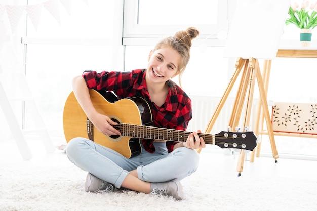 Adolescente feliz tocando guitarra em uma sala iluminada