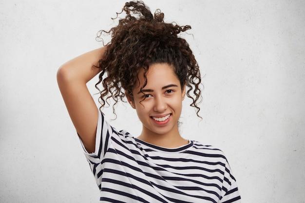 Adolescente feliz vestida casualmente, tem cabelo escuro crespo, sente-se despreocupada por ter passado em todos os exames com sucesso.