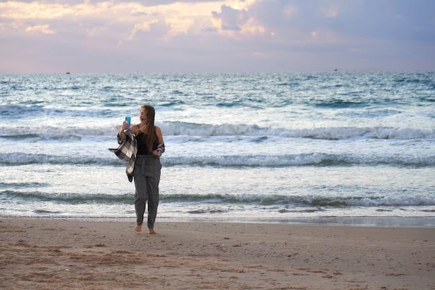 Adolescente feliz vestindo uma camisa balançando ao vento leva uma selfie à beira-mar ao pôr do sol retroiluminado com os raios do sol poente.
