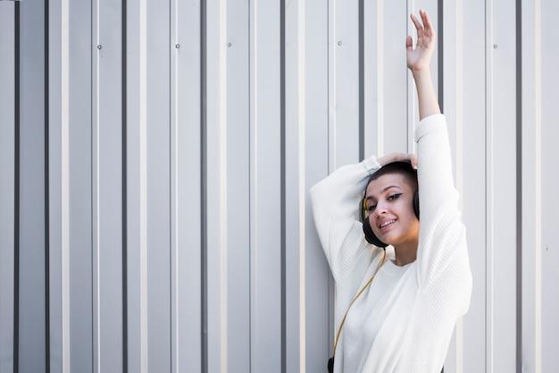 Adolescente feminino alegre em fones de ouvido com o braço levantado