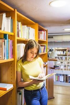 Adolescente feminino, apoiando-se na estante e lendo