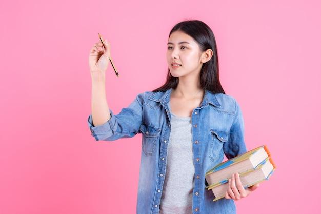 Adolescente feminino segurando livros nos braços e usar lápis