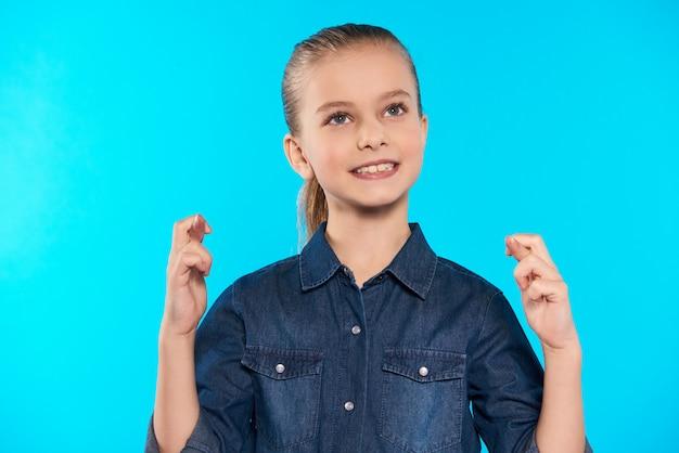 Adolescente fica com os dedos cruzados.