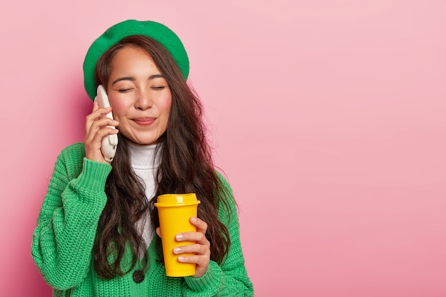 Adolescente fofa e satisfeita aprecia uma conversa agradável com uma pessoa próxima, segura o telefone celular, segura uma xícara de café amarela, usa tecnologias modernas, usa roupas verdes