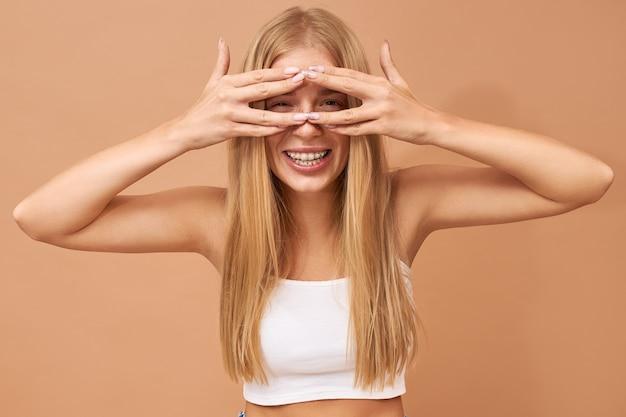 Adolescente fofa elegante com cabelo loiro usa jeans e blusa branca