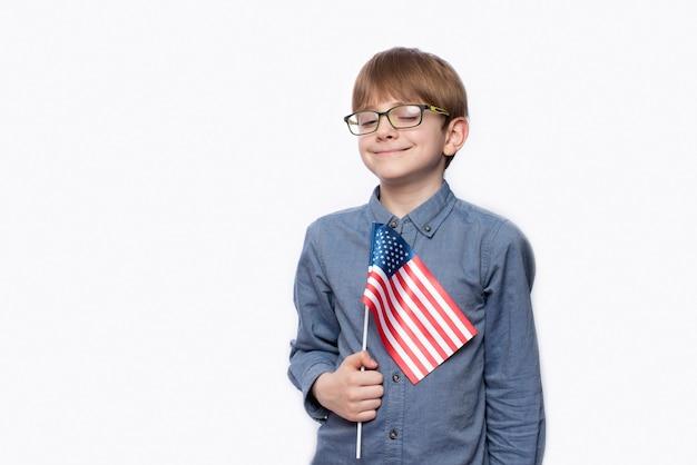 Adolescente fofo sério de óculos com a bandeira americana na parede branca isolada