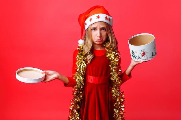 Adolescente frustrada no chapéu de papai noel e enfeites de natal na caixa de abertura do pescoço,