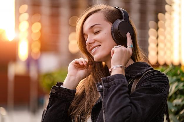 Adolescente gosta e ouve música em fones de ouvido sem fio pretos enquanto caminha pela cidade