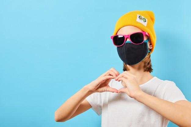 Adolescente hippie em óculos da moda, usando chapéu de malha, mostrando um gesto de coração. jovem na parede azul.