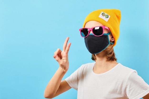 Adolescente hippie em óculos da moda, usando chapéu de malha, mostrando um gesto de paz. jovem na parede azul.