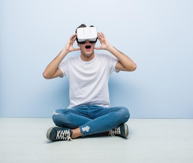 Adolescente, homem, caucasiano, usando óculos de realidade virtual, sentado no chão