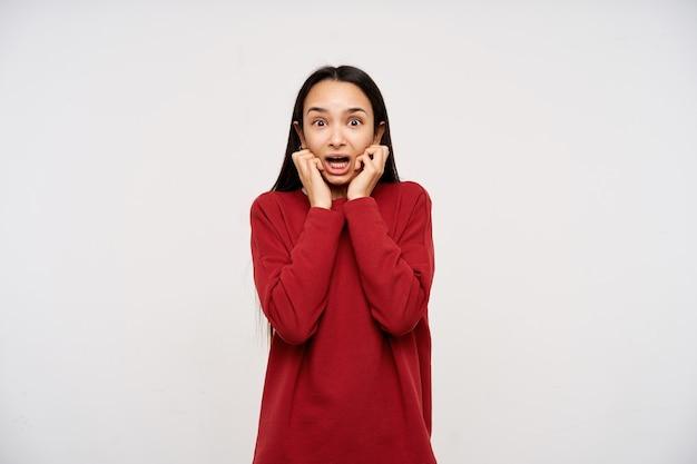 Adolescente, horrorizada olhando mulher asiática com cabelo comprido escuro. vestindo um suéter vermelho e tocando seu rosto com medo. com medo do que ela vê. assistindo a câmera isolada sobre fundo branco