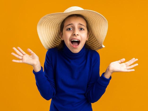 Adolescente impressionada com chapéu de praia olhando para a frente e mostrando as mãos vazias isoladas em uma parede laranja