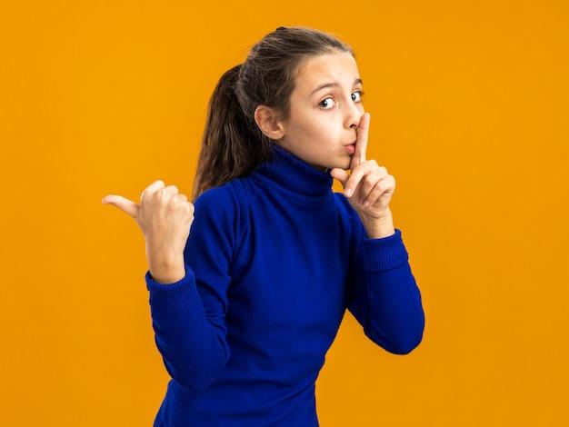 Adolescente impressionada de pé em vista de perfil, olhando para frente, fazendo gesto de silêncio, apontando para o lado isolado na parede laranja com espaço de cópia
