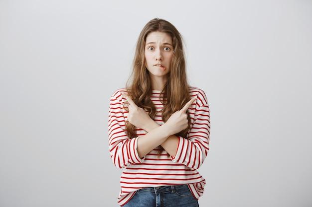 Adolescente indecisa e intrigada apontando o dedo para o lado, não sei o que escolher