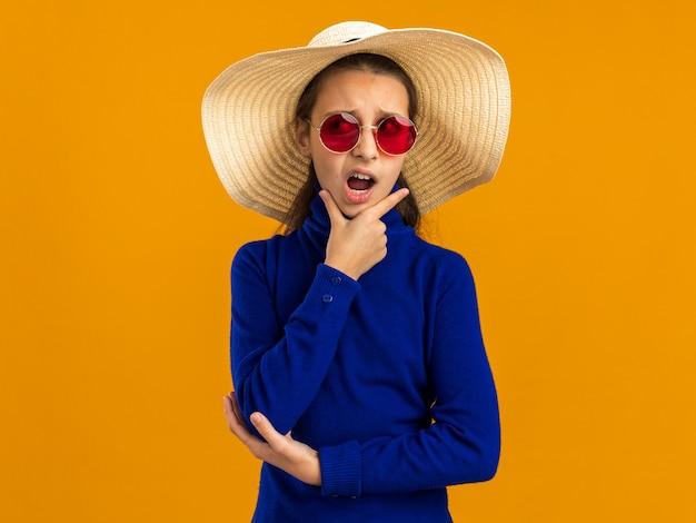 Adolescente irritada usando óculos escuros e chapéu de praia, segurando o queixo, olhando para o lado isolado na parede laranja com espaço de cópia