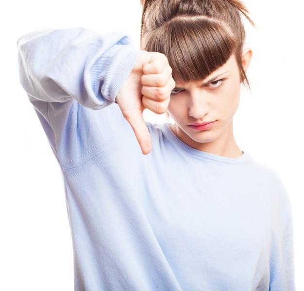 Adolescente irritado que mostra o polegar para baixo