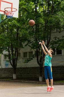 Adolescente jogando basquete chutando a bola na cesta enquanto tenta fazer um gol