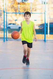 Adolescente jogando basquete em uma quadra ao ar livre