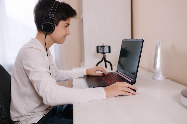 Adolescente jogando em seu computador pc na sala branca