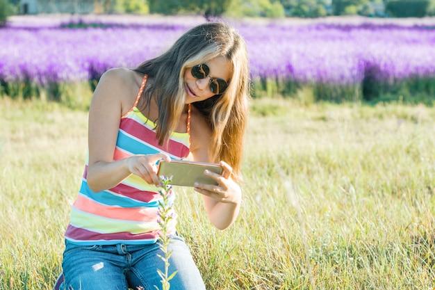 Adolescente jovem, andar, em, natureza, fotografias, planta flor, ligado, móvel, smartphone