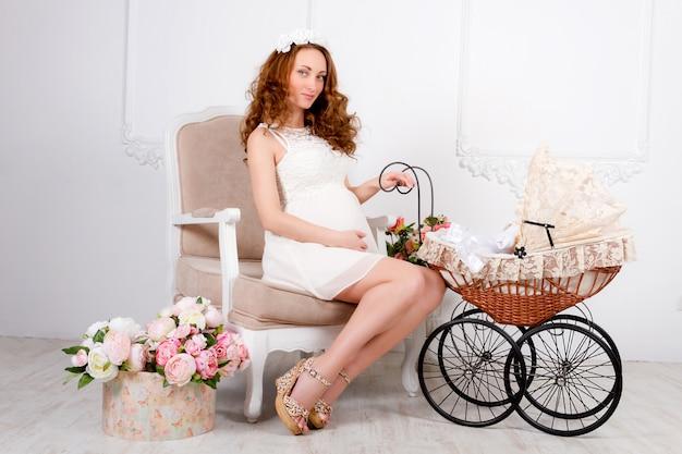 Adolescente jovem mulher bonita no vestido branco com carrinho de bebê está sentado na cadeira clássica macia