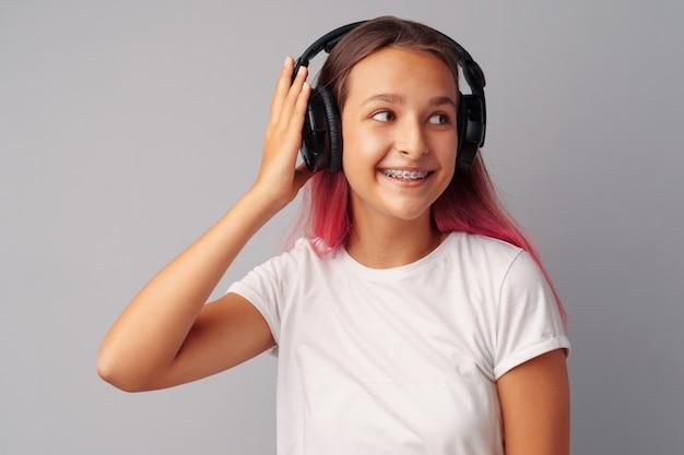Adolescente jovem ouvindo música com seus fones de ouvido sobre um cinza