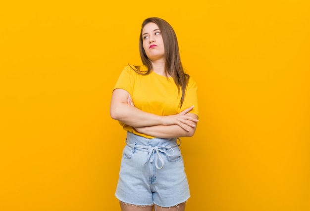 Adolescente jovem vestindo uma camisa amarela cansado de uma tarefa repetitiva.