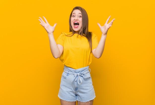 Adolescente jovem vestindo uma camisa amarela comemorando uma vitória ou sucesso, ele está surpreso e chocado.