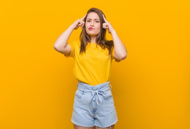 Adolescente jovem vestindo uma camisa amarela focada em uma tarefa, mantendo os dedos apontando a cabeça.