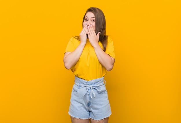 Adolescente jovem vestindo uma camisa amarela rindo de algo, cobrindo a boca com as mãos.