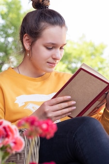 Adolescente lê livro no jardim