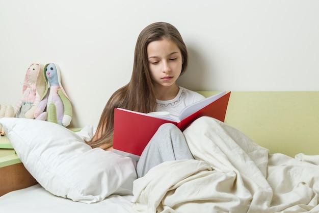 Adolescente lê um caderno de escola em cima da cama.
