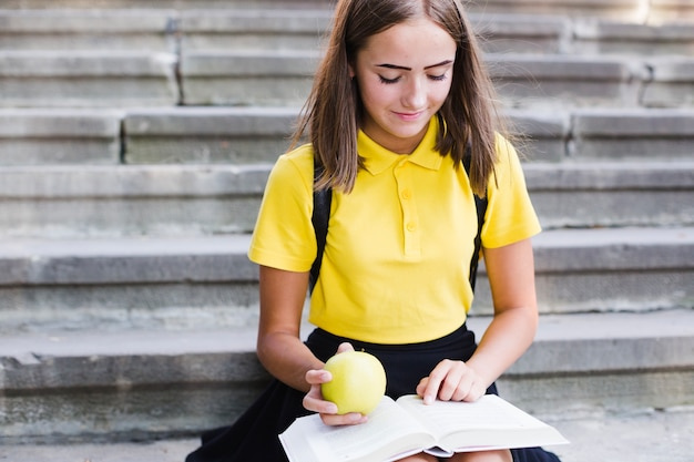 Adolescente lendo livro e d comendo maçã
