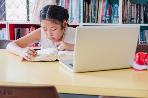 Adolescente lendo o livro com o computador portátil na biblioteca. conceito de educação e alfabetização