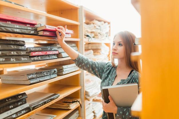 Adolescente, levando, livros, de, estante de livros