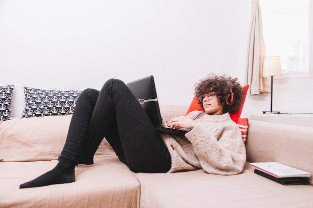 Adolescente, ligado, sofá, escutar música, e, usando computador portátil