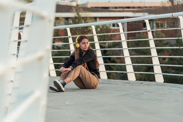 Adolescente loira com fones de ouvido amarelos, ouvindo música enquanto está sentado em uma ponte urbana branca.