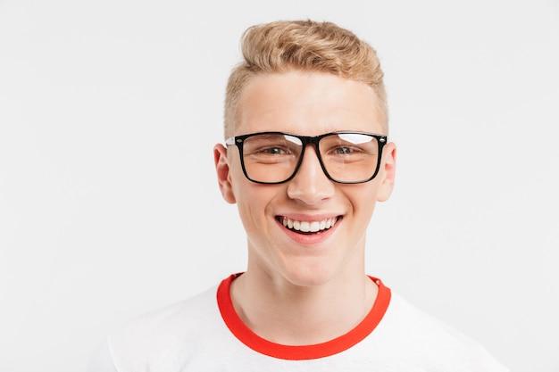Adolescente loiro, tendo a pele limpa e saudável usando óculos sorrindo com dentes brancos, isolados no branco Foto Premium